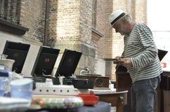 Uomo anziano che vende roba antica nel mercato delle pulci Fotografia Stock