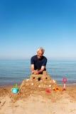 Uomo anziano con il castello della sabbia Immagini Stock Libere da Diritti