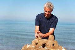 Uomo anziano con il castello della sabbia Fotografie Stock Libere da Diritti