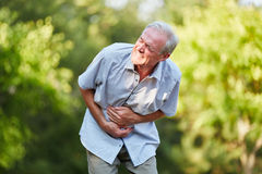 Uomo anziano con il dolore di stomaco immagine stock