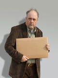 Uomo anziano con il segno sudicio della holding dei capelli Fotografia Stock