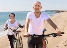 Uomo anziano con la donna in camice bianche che cammina con le biciclette sopra fotografie stock