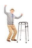 Uomo anziano con un camminatore che solleva le sue mani Immagini Stock