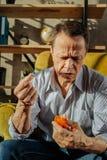 Uomo anziano dai capelli corti in una camicia a strisce osservando il nome delle pillole immagine stock