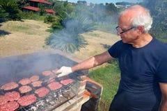 Uomo anziano del barbecue che cucina la carne del BBQ Immagine Stock Libera da Diritti