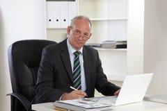 Uomo anziano di affari con il computer portatile Immagine Stock