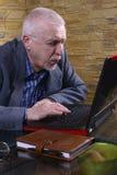 Uomo anziano di affari sul computer portatile Immagini Stock