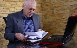 Uomo anziano di affari sul computer portatile Fotografia Stock Libera da Diritti