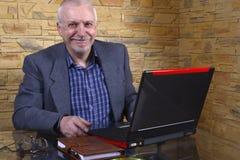 Uomo anziano di affari sul computer portatile Immagini Stock Libere da Diritti