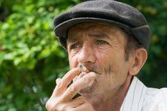 Uomo anziano di fumo Fotografie Stock