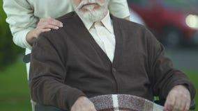 Uomo anziano di spinta femminile in sedia a rotelle, nella cura e nella pietà nella professione d'infermiera, primo piano stock footage