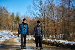 Uomo anziano e nipote che camminano nella campagna Fotografie Stock Libere da Diritti
