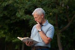 Uomo anziano emotivo con il libro Fotografie Stock Libere da Diritti