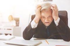 Uomo anziano esaurito afflitto circa il lavoro Immagine Stock Libera da Diritti