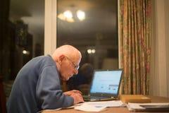 Uomo anziano facendo uso di un computer portatile per controllare le sue finanze, Hampshire, Inghilterra, U k immagine stock libera da diritti
