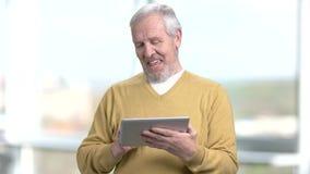 Uomo anziano felice che per mezzo della compressa del pc archivi video