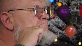 Uomo anziano felice che pettina la sua barba grigia con il pettine su fondo dell'albero di Natale in ghirlande, palle verdi del U video d archivio