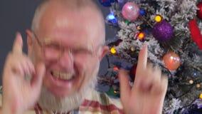Uomo anziano felice che pettina la sua barba grigia con il pettine su fondo dell'albero di Natale in ghirlande, palle verdi del U archivi video