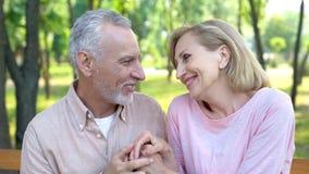 Uomo anziano felice e donna che si guardano con amore e che si tengono per mano, data fotografia stock libera da diritti