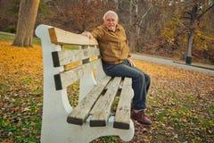 Uomo anziano felice sul banco Fotografia Stock Libera da Diritti
