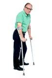 Uomo anziano fisicamente disabile con le grucce Fotografie Stock Libere da Diritti
