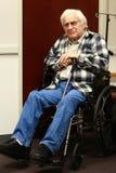Uomo anziano nei sorrisi della sedia a rotelle Immagine Stock