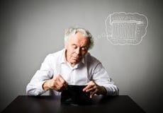 Uomo anziano nel bianco e nel periodo di riscaldamento radiatore fotografia stock libera da diritti