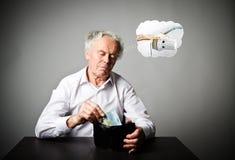Uomo anziano nel bianco e portafoglio con l'euro venti Periodo di riscaldamento, tasse e concetto di risparmio radiatore fotografia stock