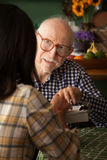 Uomo anziano nella casa con il fornitore o il acquirente di indagine Immagini Stock Libere da Diritti