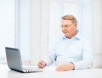 Uomo anziano in occhiali che riempiono una forma a casa Immagine Stock