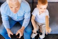 Uomo anziano piacevole che gioca i video giochi fotografie stock