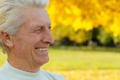 Uomo anziano piacevole che si leva in piedi su un colore giallo Immagine Stock