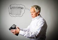 Uomo anziano in portafoglio bianco e vuoto Uomo anziano nel bianco e nel periodo di riscaldamento radiatore immagine stock