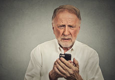 Uomo anziano preoccupato che esamina il suo Smart Phone Fotografia Stock