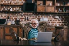 Uomo anziano rilassato in cuffie facendo uso del computer portatile con i piedi fotografia stock libera da diritti