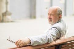 Uomo anziano rispettabile che si siede su un banco Fotografia Stock