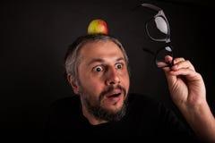 Uomo anziano scontroso sembrante pazzo con la barba grigia e grandi vetri con la mela Fotografia Stock Libera da Diritti