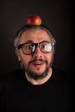 Uomo anziano scontroso sembrante pazzo con la barba grigia e grandi vetri del nerd con la mela Immagini Stock