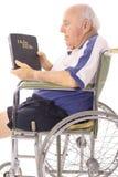 Uomo anziano in sedia a rotelle che legge una bibbia immagine stock