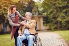 Uomo anziano in sedia a rotelle con sua figlia che gode di visitare a immagini stock libere da diritti