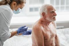 Uomo anziano senza camicia che riceve iniezione in parte posteriore mentre sedendosi sul letto di ospedale fotografia stock