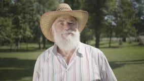 Uomo anziano sicuro con la barba bianca lunga in cappello di paglia che osserva condizione sorridente e d'ondeggiamento della mac archivi video