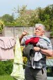 Uomo anziano sollecitato appendendo fuori la lavanderia. Fotografia Stock Libera da Diritti