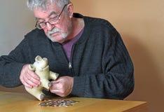 Uomo anziano sollecitato che di svuotamento porcellino salvadanaio. Fotografia Stock