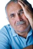 Uomo anziano solo con la mano sul suo fronte Fotografia Stock