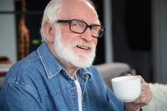 Uomo anziano sorridente con la tazza di caffè fotografia stock libera da diritti