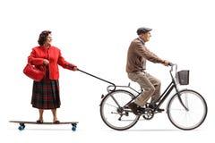 Uomo anziano su una bicicletta che tira una donna anziana su un longboard Fotografia Stock