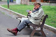 Uomo anziano sul banco Immagine Stock
