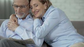 Uomo anziano sul giornale della lettura dello strato, donna che si siede accanto ad abbracciarlo, preoccupandosi archivi video