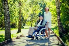 Uomo anziano sulla sedia a rotelle e sulla giovane donna nel parco Fotografie Stock Libere da Diritti